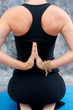 young woman in yoga Virasana  or hero pose with reverse prayer