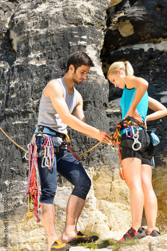 Rock climbing man showing woman rope knot