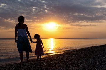 Mother and kid on sunset beach