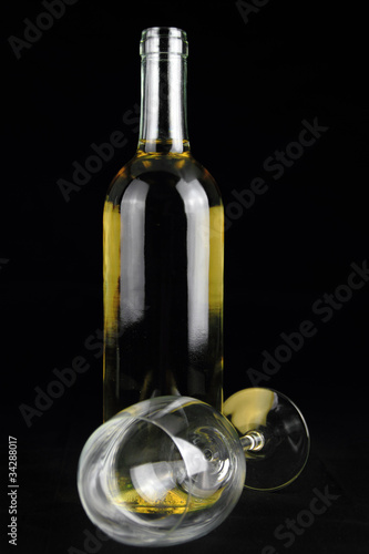Bottle of white wine and a crystal wineglass