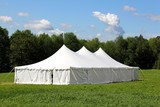 a white wedding or entertainment tent in a green field