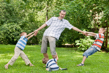 Father and three sons play in the park.
