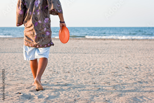play to frisbee on the beach in summer