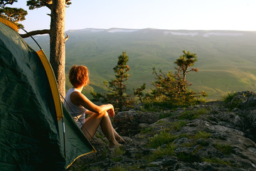 woman sit next to the tent