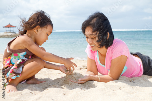 mother and child playing with beach sand