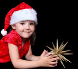 close-up of sweet little girl in santa hat laying on floor with
