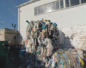 Large pressed polythene heaps prepared for recycling.