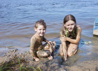 Children in the mud on the river