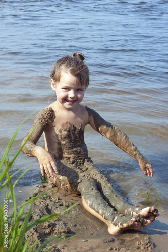 Baby girl in the mud on the river