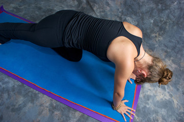 looking down on woman doing low lunge on yoga mat in studio