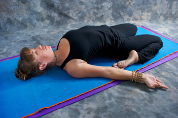 woman on mat in studio doing yoga posture reclined hero pose
