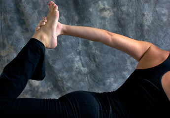 close up of woman doing half bow yoga pose
