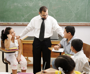 happy children learning with teacher in school