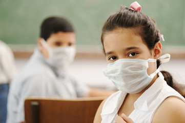 Children in classroom with masks on faces, virus up!