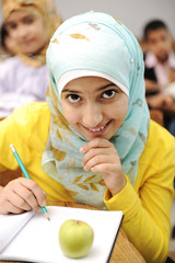 happy children in school, classroom, girl sitting