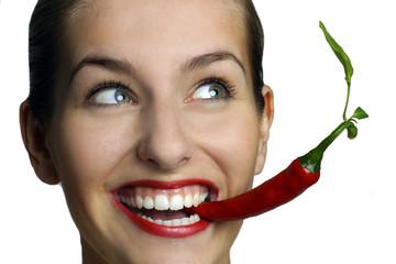 Junge Frau mit Chilischote im Mund
