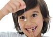 Lost milk-tooth, cute boy holding his tooth on thread