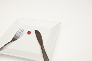 Single small tomato on a white plate with a white background