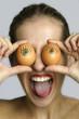 Junge Frau hält sich zwei Eier vor die Augen