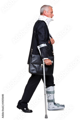 Injred businessman on crutches isolated on white