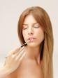 beautiful woman applying lipstick with brush