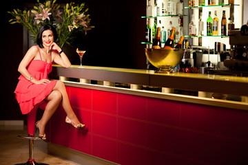 woman red dress at bar counter smiling