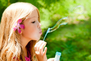 Children blowing soap bubbles in outdoor forest
