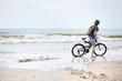 Young man bicycling along al beach, Baltic sea