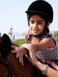 bambina accarezza dorso del cavallo