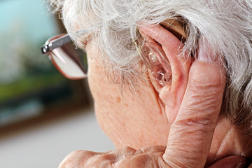 aged woman with glasses and hearing aid