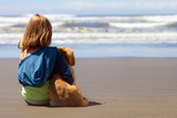 child at the beach with her puppy