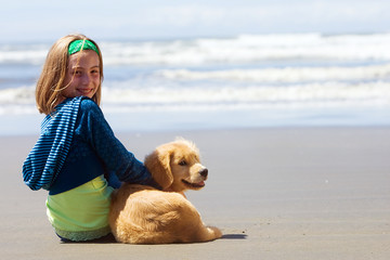 child with a puppy at the beach