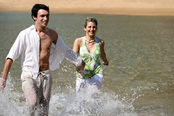 Playful young couple running through water