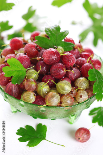 Fresh gooseberry and green leaves on white background isolated