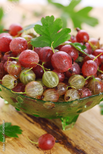 Fresh gooseberry and green leaves on wooden background