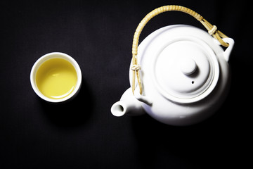 Tea pot and cup full of green tea