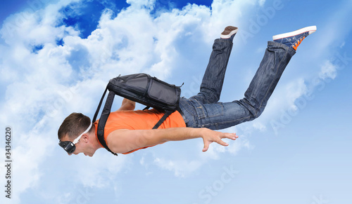 Extreme flight man with a parachute in the clouds
