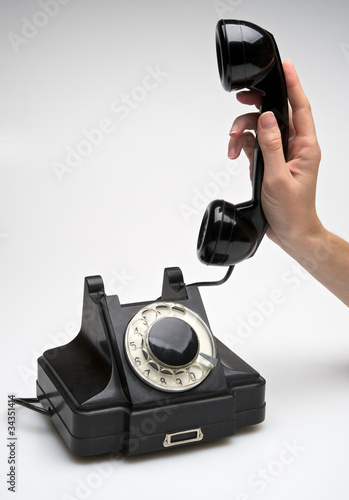 Vintage telephone being picked up