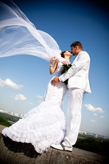 newly married couple kissing.wind lifting white bridal veil