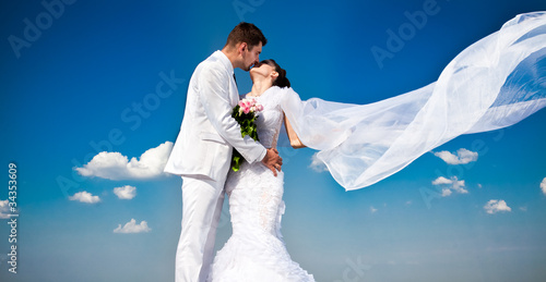 newly married couple.wind lifting long white bridal wedding