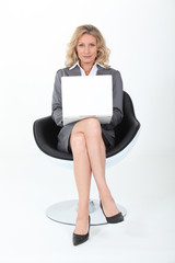 Businesswoman sat in modern chair with laptop computer