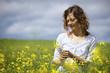 Woman picking yellow flowers in field.
