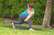 woman doing Yoga pose bound low lunge outdoors on grass