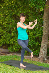woman doing Yoga pose dancing shiva outdoors on grass