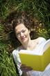 Woman lying in meadow reading
