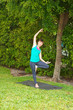woman doing Yoga pose tree variation outdoors on grass