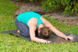 woman doing Yoga posture Balasana or childs pose outdoors on gra