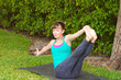 young woman doing Yoga pose Navasana variation or boat pose outd