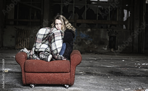 Sad girl in shabby sofa