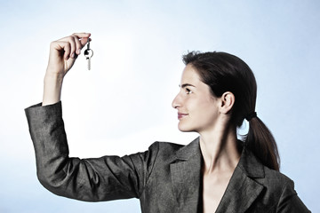 Profile of woman holding key between fingers